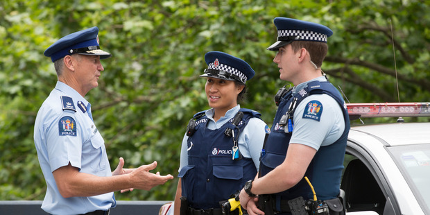 Commissioner of New Zealand Police Mike Bush talks with Police Constables Trish Fatu and Jackson Hood, during his visit to Auckland Central Police Station. Photo / Brett Phibbs